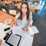 Muchacha que estudia en la cantina de universidad Foto de archivo libre de regalías