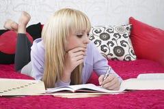 Muchacha que estudia mientras que miente en cama Imágenes de archivo libres de regalías
