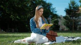 Muchacha que estudia sus notas Mujer joven que se sienta en la hierba en el parque, sosteniendo un cuaderno abierto, mirando lejo almacen de video