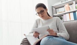 Muchacha que estudia y que conecta con una tableta Foto de archivo libre de regalías