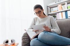 Muchacha que estudia y que conecta con una tableta Imagen de archivo