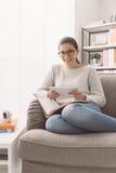 Muchacha que estudia y que conecta con una tableta Fotografía de archivo