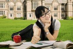 Muchacha que estudia y que miente en el patio de escuela Foto de archivo