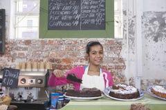 Muchacha que exhibe los pasteles en tienda Imágenes de archivo libres de regalías