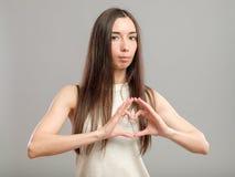Muchacha que forma el corazón con sus manos Fotografía de archivo libre de regalías