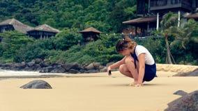 Muchacha que fotografía en la playa fotos de archivo libres de regalías