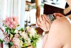 Muchacha que fotografía en las flores de la boda del teléfono móvil Imagen de archivo