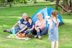 Muchacha que fotografía a la familia en el sitio para acampar Imágenes de archivo libres de regalías