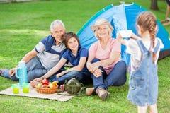 Muchacha que fotografía a la familia en el sitio para acampar Imagen de archivo libre de regalías