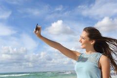 Muchacha que fotografía un selfie con un teléfono elegante en la playa Imagen de archivo libre de regalías