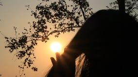 Muchacha que frota ligeramente el pelo en la puesta del sol metrajes