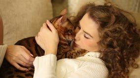 Muchacha que frota ligeramente y que besa su gato de Bengala metrajes