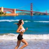Muchacha que funciona con a San Francisco Golden Gate Bridge Fotografía de archivo libre de regalías
