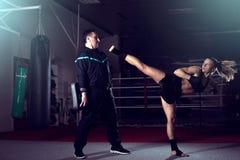 Muchacha que golpea detrás la pierna con el pie durante práctica kickboxing fotografía de archivo libre de regalías