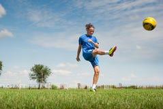 Muchacha que golpea el balón de fútbol con el pie Foto de archivo