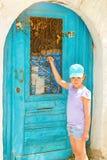 Muchacha que golpea en puerta azul Rethymno, Creta Grecia Fotos de archivo