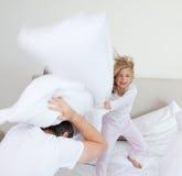 Muchacha que golpea a su padre con la almohada Fotos de archivo