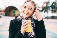 Muchacha que goza del café de la mañana en un parque Fotografía de archivo