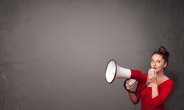 Muchacha que grita en el megáfono en fondo del espacio de la copia Foto de archivo libre de regalías