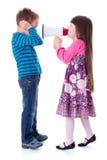 Muchacha que grita en el muchacho con el megáfono Foto de archivo