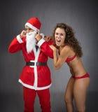 Muchacha que grita en los oídos de Papá Noel Fotos de archivo