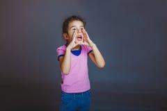 Muchacha que grita lejos en fondo gris Imágenes de archivo libres de regalías