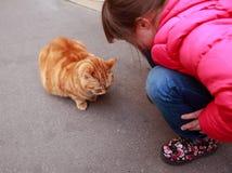 Muchacha que habla con el gato Fotos de archivo