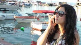 Muchacha que habla con el teléfono móvil en un muelle