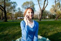 Muchacha que habla con una célula en el parque Imagen de archivo