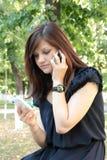 Muchacha que habla en dos teléfonos móviles Fotos de archivo