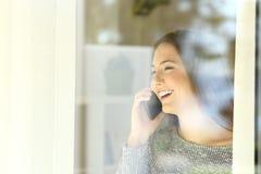 Muchacha que habla en el teléfono al lado de una ventana Fotos de archivo libres de regalías