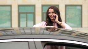 Muchacha que habla en el teléfono cerca de un coche moderno metrajes