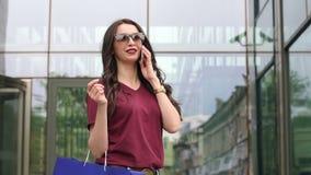 Muchacha que habla en el teléfono cerca del centro comercial metrajes