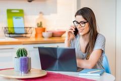 Muchacha que habla en el teléfono con el ordenador portátil en frente Fotografía de archivo