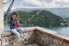 Muchacha que habla en el teléfono del top del castillo de la montaña con la opinión del valle y el lago en el fondo Copie el espa Fotografía de archivo libre de regalías
