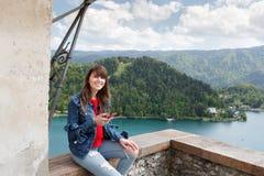 Muchacha que habla en el teléfono del top del castillo de la montaña con la opinión del valle y el lago en el fondo Copie el espa Imagen de archivo