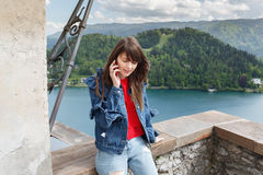 Muchacha que habla en el teléfono del top del castillo de la montaña con la opinión del valle y el lago en el fondo Copie el espa Imagen de archivo libre de regalías