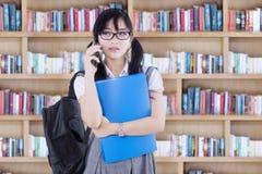 Muchacha que habla en el teléfono en biblioteca Fotos de archivo libres de regalías