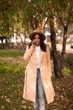 Muchacha que habla en el teléfono en el parque del otoño Imágenes de archivo libres de regalías