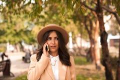 Muchacha que habla en el teléfono en el parque del otoño fotos de archivo