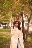 Muchacha que habla en el teléfono en el parque del otoño Imagen de archivo