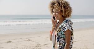 Muchacha que habla en el teléfono móvil en la playa