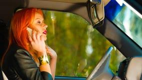 Muchacha que habla en el teléfono móvil mientras que conduce el coche Imágenes de archivo libres de regalías