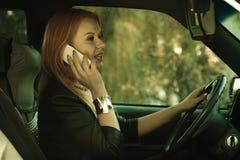 Muchacha que habla en el teléfono móvil mientras que conduce el coche Foto de archivo