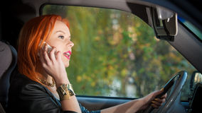 Muchacha que habla en el teléfono móvil mientras que conduce el coche Foto de archivo libre de regalías