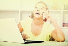 Muchacha que habla en el teléfono móvil mientras que estudia con el ordenador portátil dentro Imagenes de archivo