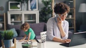 Muchacha que habla en el teléfono móvil que trabaja con el ordenador portátil mientras que su hijo que juega en casa almacen de metraje de vídeo