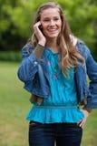 Muchacha que habla en el teléfono mientras que se coloca en un PA Fotografía de archivo libre de regalías