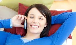 Muchacha que habla en el teléfono que miente en un sofá Fotos de archivo libres de regalías