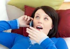 Muchacha que habla en el teléfono que miente en un sofá Fotografía de archivo